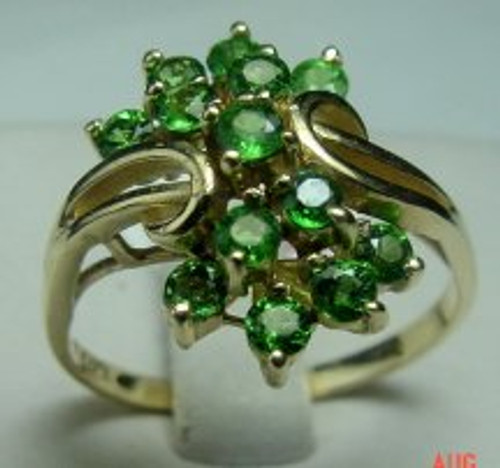This is a 14 karat yellow gold ring with ornate Tsavorite cluster. The total weight of the ring is 3.9 grams and is made for a finger size of 9