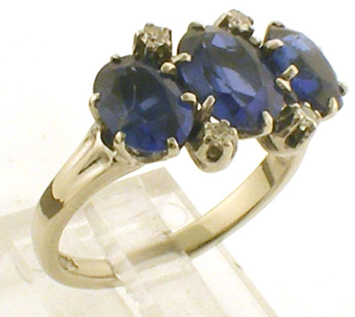 This is a 14 karat white gold ring with three synthetic blue sapphire stones and four diamonds. The total weight of the diamonds is .08ct and the total weight of the ring is 3.7 grams. The ring was made for a finger size of 6