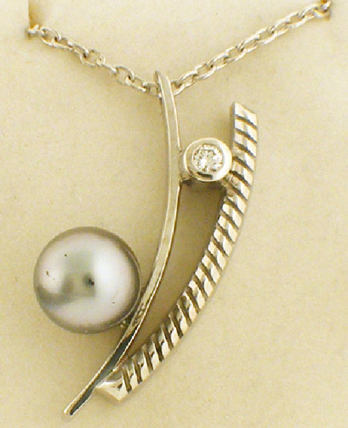 14 karat white gold custom made tahitian pearl and diamond necklace weighing 15.0 grams. (chian sold separately). Diamond weighs .14 ct. Pearl is 11.3 mm