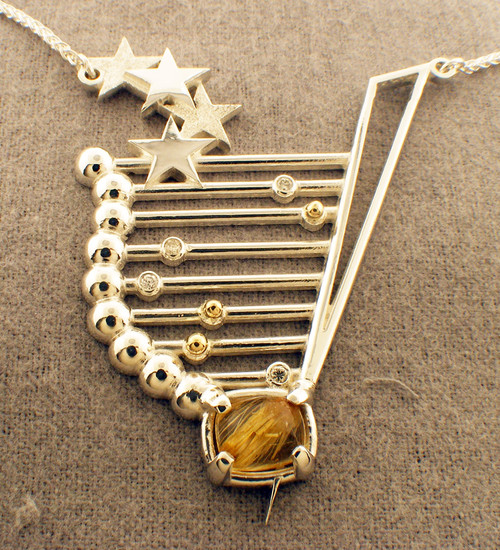 Sterling / 14k yellow gold custom made pendant. Diamonds = .18ct tw and contains a rutilated quartz.