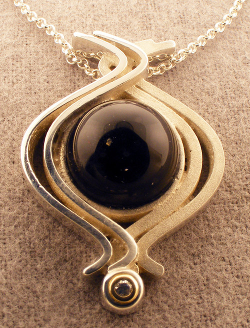 Sterling Silver , 14k yellow gold, Black onyx and diamond pendant.