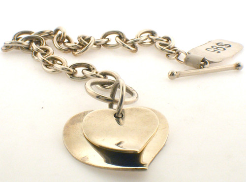 Sterling silver rolo link toggle bracelet with double heart attached. The total length of the bracelet is 7 inches and the total weight is 16.6 grams.