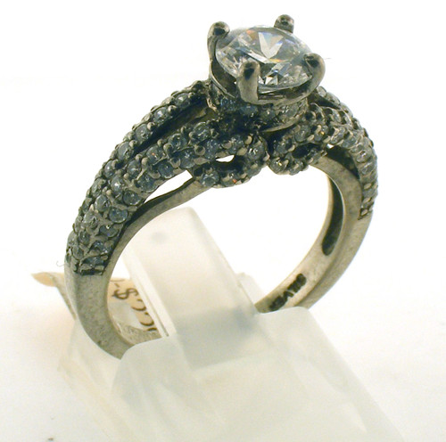 Ornate sterling silver and cz engagement style ring. The cz total weight is .80ct + ctr. The total weight of the ring is 3.8 grams and is made for a finger size of 6.5.