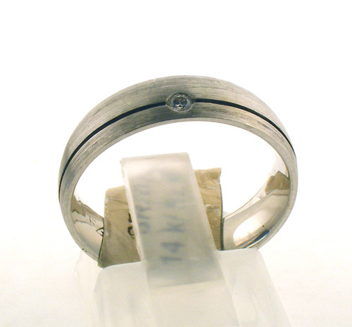 14 karat white gold and diamond wedding ring. The total weight of the ring is 5.6 grams and is made for a finger size of 6.25.