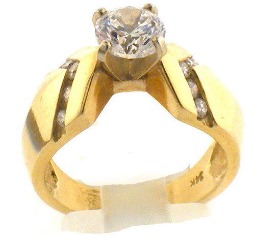 14 karat yellow gold and diamond engagement ring. The diamond TW is .21ct. Center stone is CZ but is exchangeable. The total weight of the ring is 7.0 grams and is made for a finger size of 6.25.