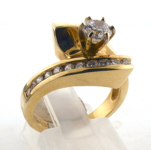 14 karat yellow gold and diamond engagement ring. The diamond TW is .23ct. Center stone is CZ but is exchangeable. The total weight of the ring is 6.6 grams and is made for a finger size of 6.25-6.5 short.