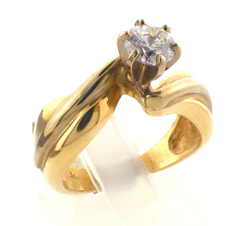 14 karat yellow gold and CZ center stone engagement ring. The total weight of the ring is 7.6 grams. This is made for a finger size of 7.