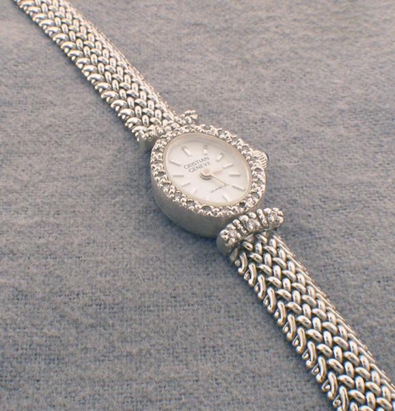 14Karat white gold Cristian Geneve watch. Watch weighs 27.7 grams and Dia weight is 17.8 dwt. The length of the watch is 7 inches.