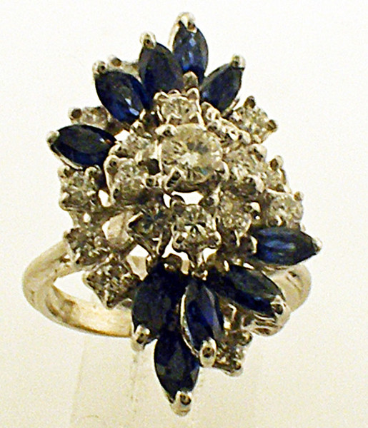 This is a 14 karat white gold cocktail ring. The ring includes both genuine sapphires and diamonds. The total weight of the ring is 8.6 grams and is for a finger size of 6.75