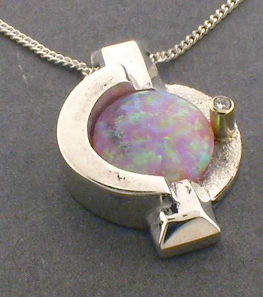 Sterling silver and 14karat yellow gold simulated opal pendant.