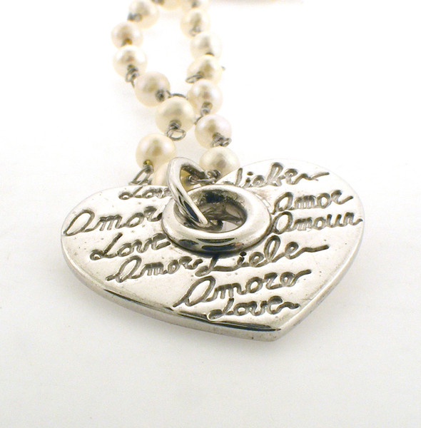 Sterling silver and pearl heart pendant with inscriptions on the heart. The total weight of the pendant is 11.5 grams.
