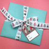 Make your presents extra special with this fun ribbon tied on non traditional colored paper for a fun twist on Christmas gift wrap!