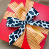 Our cow print ribbon paired with  our red and yellow plaid makes for the perfect Toy Story  themed  gift wrap!