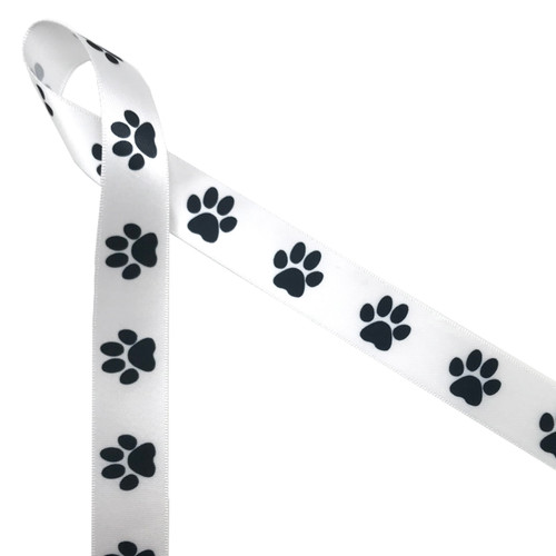 "Black paw prints printed in 7/8"" white single face satin ribbon is such a fun ribbon for all your pet themed projects. Be sure to have this ribbon on hand for special doggie treats too!"