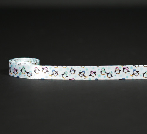 """Penguins wearing their Winter hats and scarves dance along our 5/8"""" ribbon among the blue snowflakes! Designed and printed in the USA"""