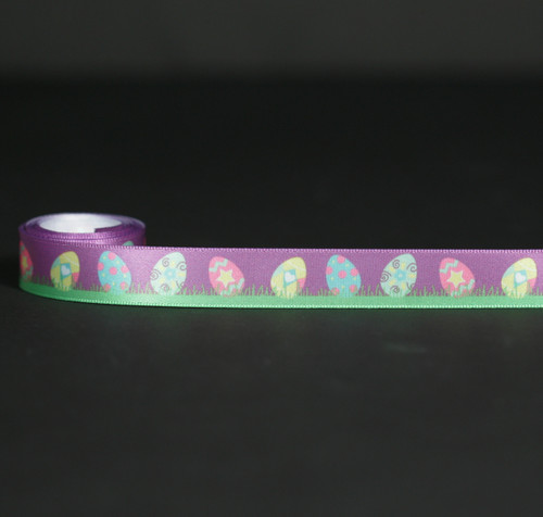 "Eggs in the Grass with a purple background printed on 5/8"" white single face satin ribbon. Designed and printed in the USA"