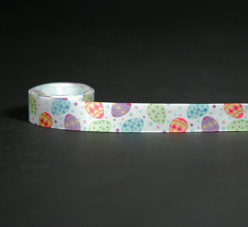 "Tossed Eggs on 5/8"" white single face satin ribbon features all the fun of Easter colors! Make this sweet ribbon part of your Easter celebrations!"
