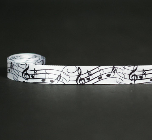 "Musical notes in black on their staff dance along a 5/8"" white single face satin ribbon. Offered in 10 and 90 yard spools. Designed and printed in the USA"