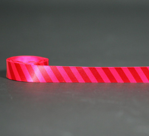 "Red stripes on hot pink 5/78"" single face satin ribbon is a bold and fun ribbon for tying small boxes and favors."
