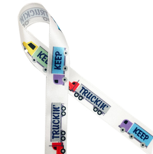 """Keep Truckin with red, yellow, blue and green trucks printed on 5/8"""" white satin ribbon. Keep Truckin ribbon honors our hard working truck drivers who are critical to our supply chain of food, medicine and other essentials. Be sure to have this ribbon on hand for your favorite trucker!"""