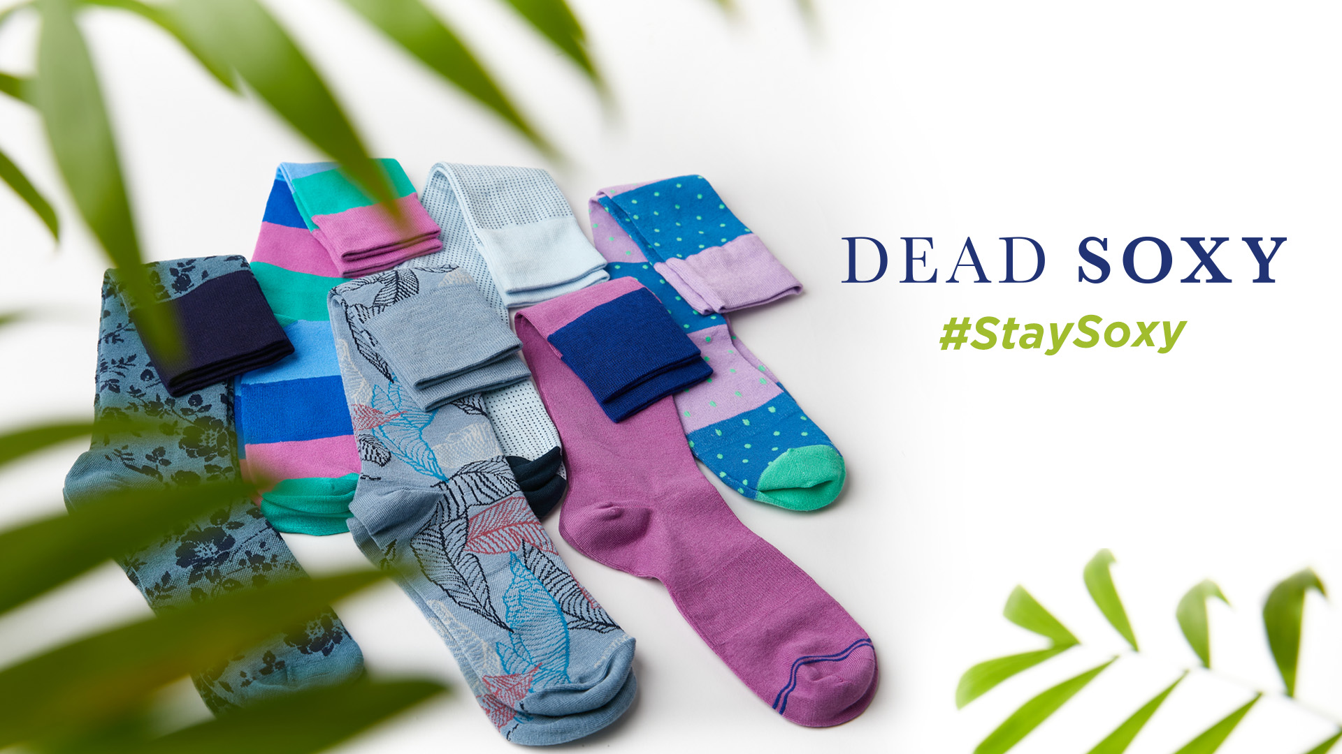premium bamboo dress socks laid out behind plant leaves with deadsoxy