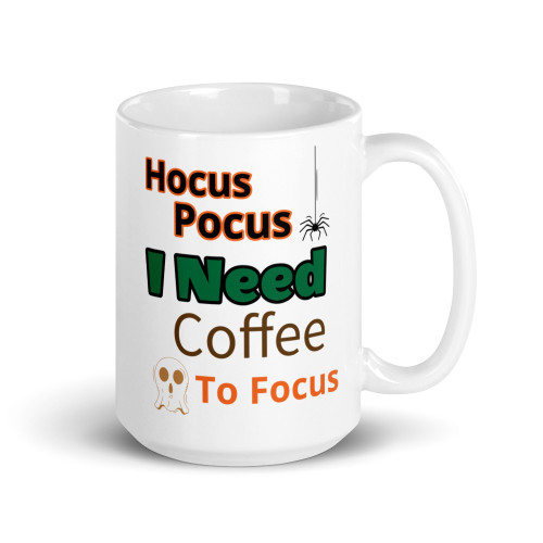 Right side of all white coffee mug with hocus pocus I need coffee to focus on it.
