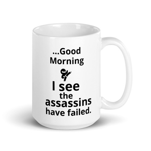 Right side of all white coffee mug with good morning I see the assassins have failed on it.