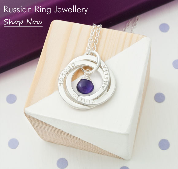 personalised russian 3-ring pendant with birthstone on wooden block