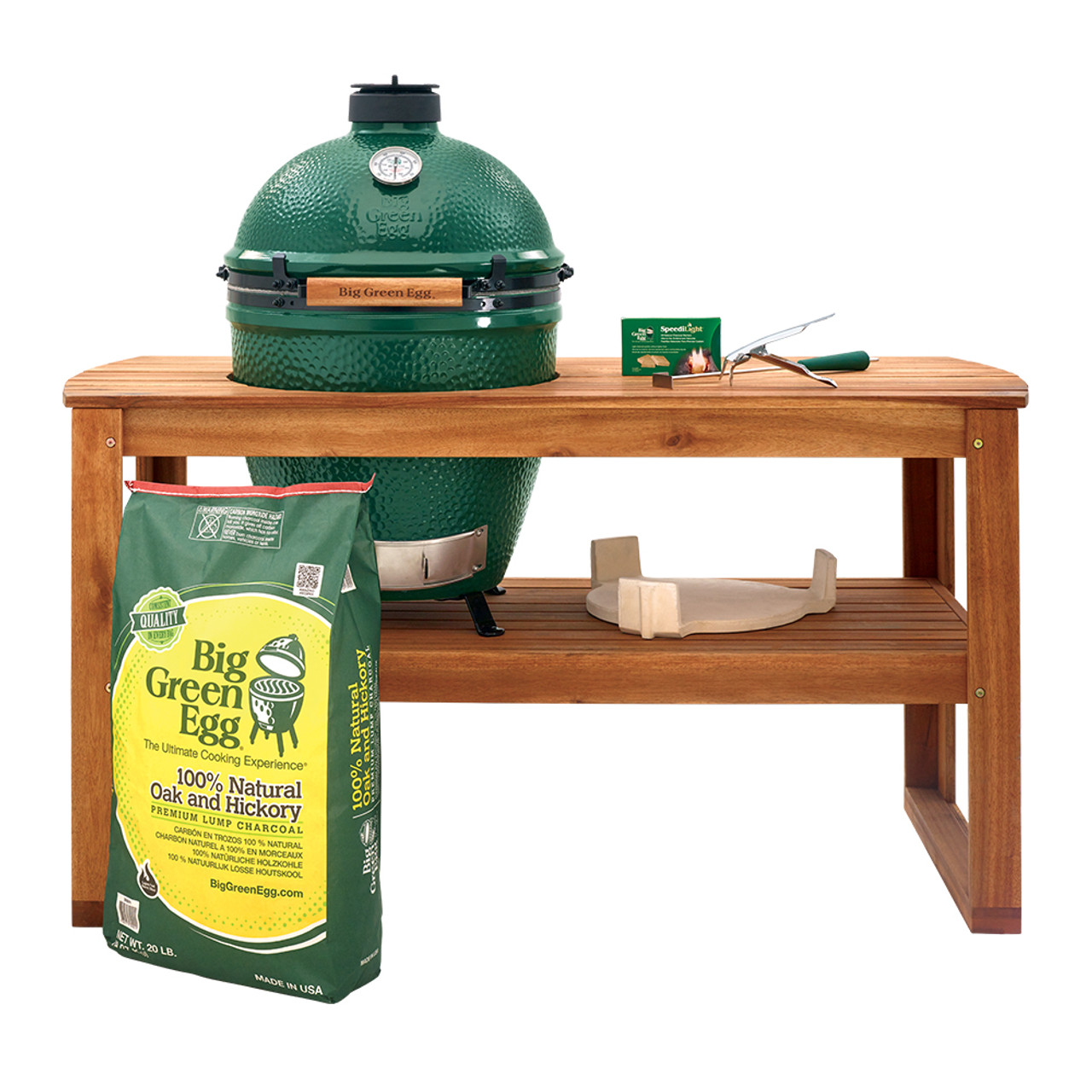 Large Big Green Egg housed in an acacia wood table and table nest, along with common tools and EGGsessories for cooking and maintenance