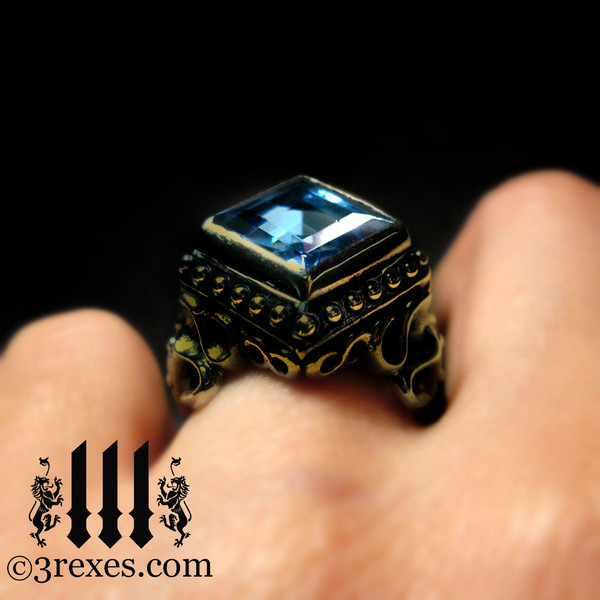 raven love brass wedding ring with large blue topaz stone