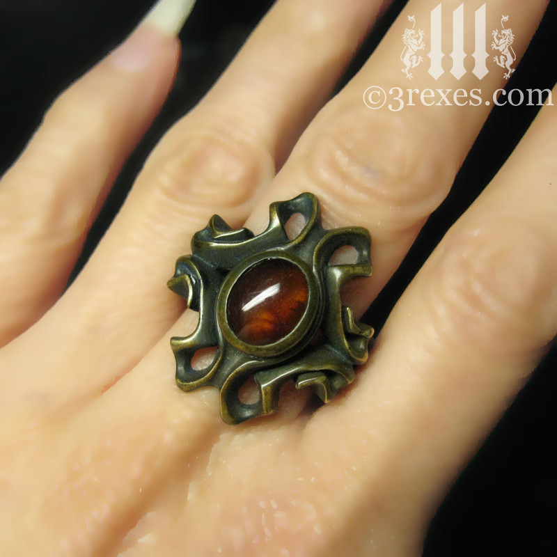 empress vampire brass ring with amber cabochon on middle finger