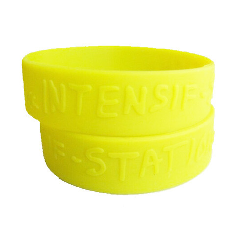 wide style custom embossed silicone wristband in the color yellow and no color fill in design.