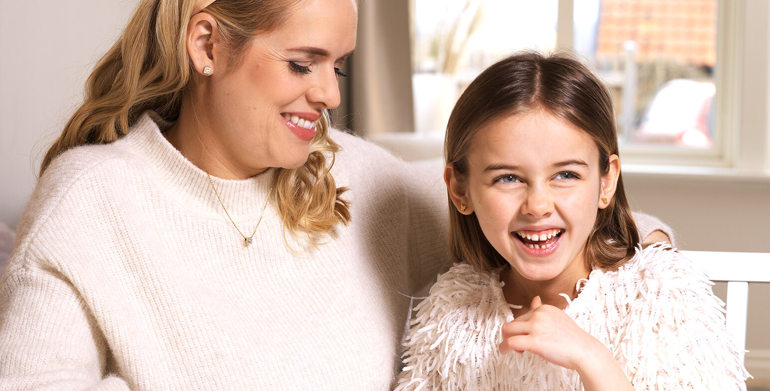 Mother & Daughter Wearing Blomdahl Earrings And Smiling