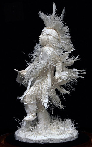 """Side view of, """"Little Fancy Dancer,"""" cast paper sculpture by Patty Eckman which features a young Native American dancing in full regalia."""