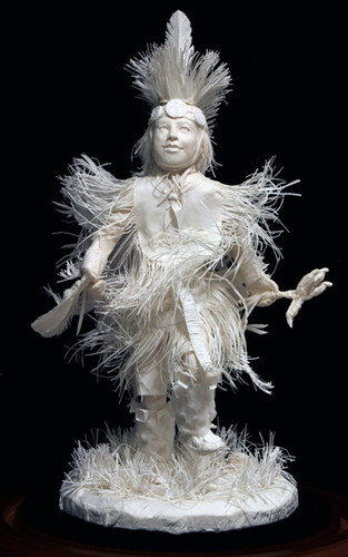 """Front view of, """"Little Fancy Dancer,"""" cast paper sculpture by Patty Eckman featuring a young Native American dancing in full regalia."""