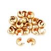 2.5mm bulk pile of 12kt gold crimp covers for custom jewelry making.