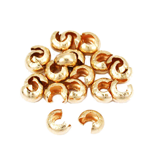 2.5mm bulk pile of 12kt gold crimp covers for custom jewelry making.