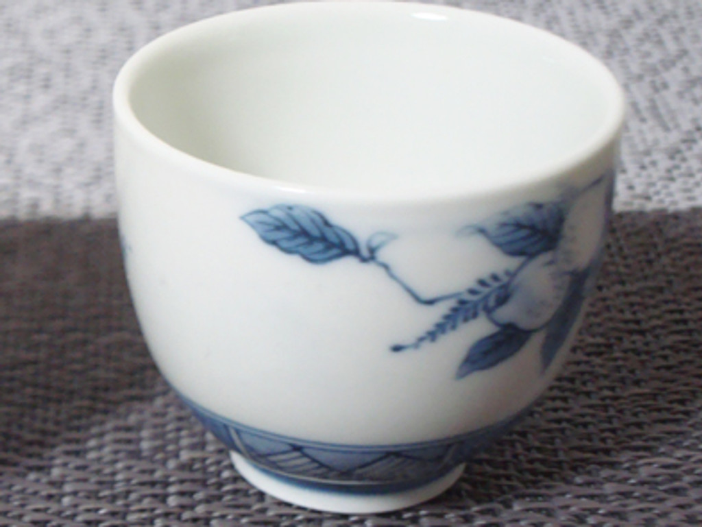 This is an Old Arita ware, sake cup.  Peach trees and peaches are delicately delineated in the sake cup.