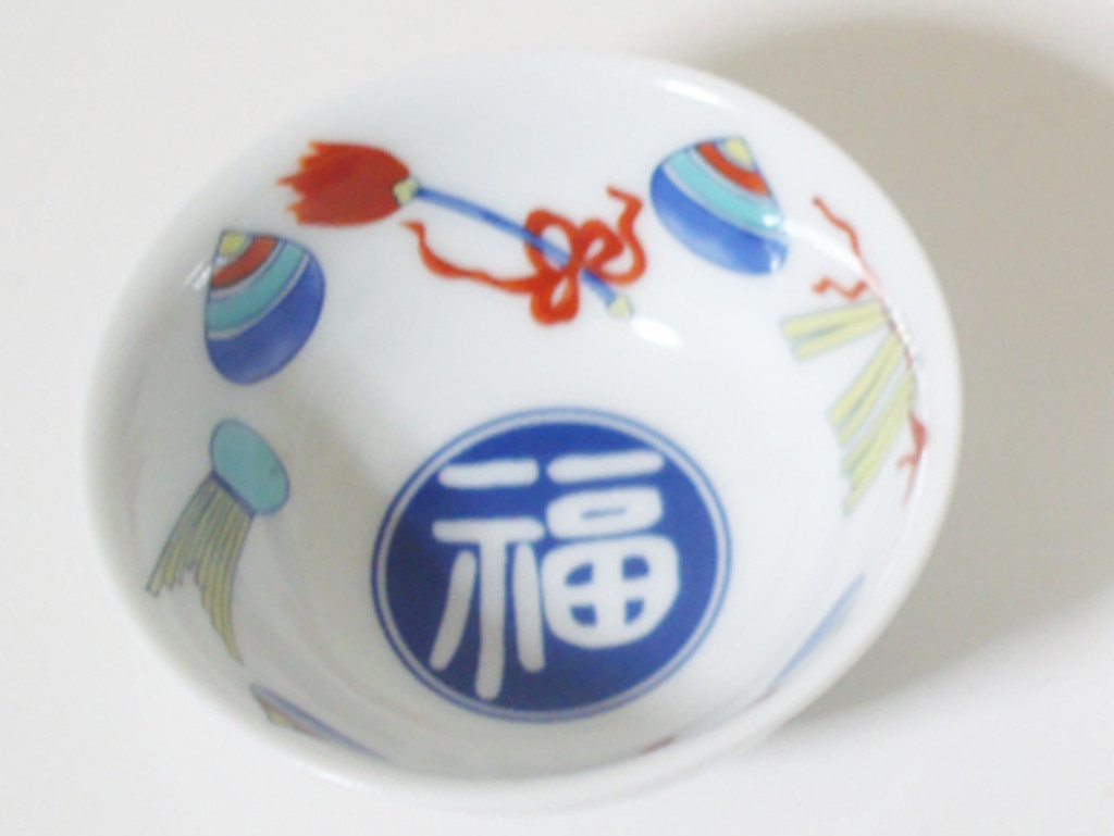 This is an Arita ware, sake cup with a color painting of abundant treasure of good fortune. This cup has delicate pictures drawn by skilled craftsmen.