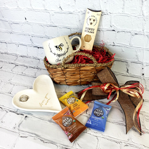 """Relax and Bee Happy Gift Basket filled with Honey Straws, Assorted Tea Drops, Bee Happy Coffee mug and heart shaped """"Love you more"""" tray all displayed in a beautiful handmade seagrass basket"""