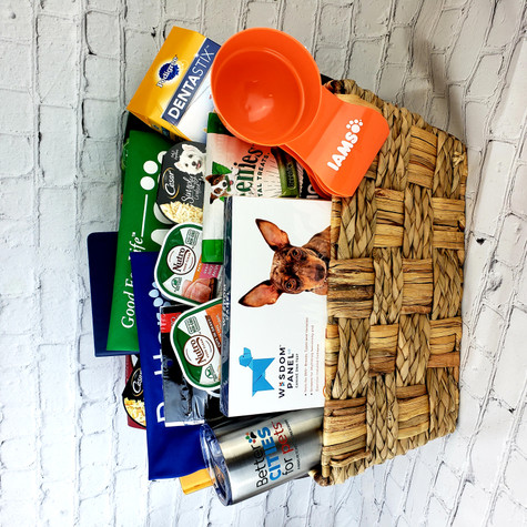 Deluxe Dog Basket includes Better Cities for Pets Insulated Cup, Notebook, Water bowl and Bandana, Iams Bandana, Iams Scoop, Dogs Rule Book, Wisdom Panel, Nutro Dry Dog Food, Iams Dry Dog Food, Dentistix treats, Greenies Treats, Cesar Treats, Nutro Crunchy Treats, (2) Two Packages of Nutro Wet Food and (2) Two Packages of Cesar Simply all Displayed in a decorative seagrass basket.    Shown with Wisdom Panel Kit
