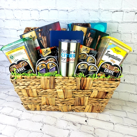 Decorative Seagrass basket filled with Better Cities for Pets Notebook and Insulated Mug, Crave Dry Food, Iams Dry Food, (2) Two Sheba Meaty Tender Sticks, Large Greenies Tub, Large Temptations Tub (2) Two Sheba Broths, (2) Two Crave Wet Food and (4) Four Sheba Wet Food.