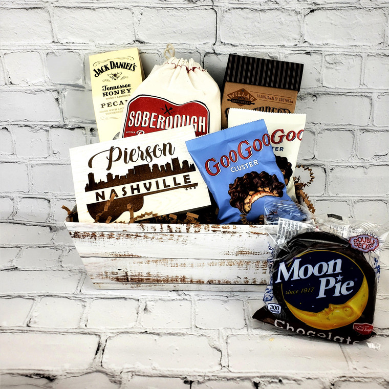 Enjoy a taste of Tennessee gift including delicious Tennessee Honey Jack Daniels Pecans, Soberdough Bread Mix, Willa's shortbread, Goo Goo Clusters, Moonpie and a personalized Nashville Skyline Guitar Wood Sign