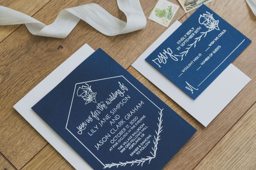 Lilies Wedding Invitation Suite Stamps by Paper Sushi. Stamped wedding invitations are the perfect way to get super expensive effects like white ink on dark paper at really reasonable pricing. #weddinginvitation