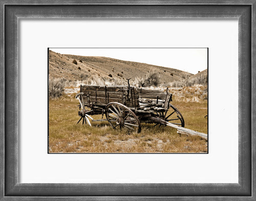 A weathered old wagon sits in a field, no longer used