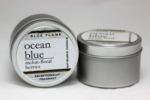 There are two silver, modern designed travel tins in the image. One tin is on it's side to show what the top of the label looks like on the lid: It says: ocean blue underlined in the middle of the label, and is off set towards the left side in large text, melon-floral-berries are written below in a smaller font. The Blue Flame logo is at the top of the label. Soy-blend Candle is written on the right side in a vertical line. On the bottom of the label is written, Exceptionally Fragrant. The other tin is flat and shows that the tin is just silver without a wrap around label. The modern design uses pale hues and simplistic lines.