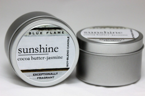 There are two silver, modern designed travel tins in the image. One tin is on it's side to show what the top of the label looks like on the lid: It says: sunshine underlined in the middle of the label, and is off set towards the left side in large text, cocoa butter-jasmine is written below in a smaller font. The Blue Flame logo is at the top of the label. Soy-blend Candle is written on the right side in a vertical line. On the bottom of the label is written, Exceptionally Fragrant. The other tin is flat and shows that the tin is just silver without a wrap around label. The modern design uses pale hues and simplistic lines.