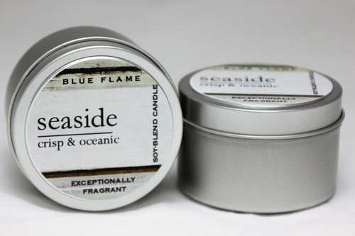 There are two silver, modern designed travel tins in the image. One tin is on it's side to show what the top of the label looks like on the lid: It says: seaside underlined in the middle of the label, and is off set towards the left side in large text, crisp & oceanic are written below in a smaller font. The Blue Flame logo is at the top of the label. Soy-blend Candle is written on the right side in a vertical line. On the bottom of the label is written, Exceptionally Fragrant. The other tin is flat and shows that the tin is just silver without a wrap around label. The modern design uses pale hues and simplistic lines.