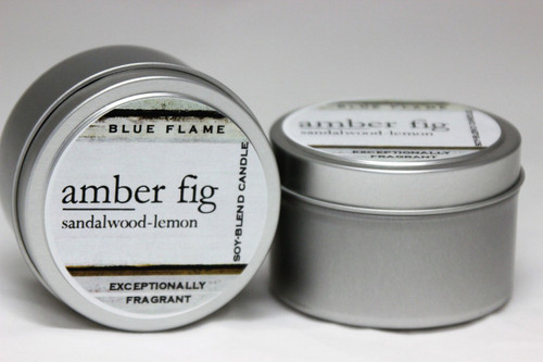 There are two silver, modern designed travel tins in the image. One tin is on it's side to show what the top of the label looks like on the lid: It says: amber fig underlined in the middle of the label, and is off set towards the left side in large text, sandalwood-lemon is written below in a smaller font. The Blue Flame logo is at the top of the label. Soy-blend Candle is written on the right side in a vertical line. On the bottom of the label is written, Exceptionally Fragrant. The other tin is flat and shows that the tin is just silver without a wrap around label. The modern design uses pale hues and simplistic lines.
