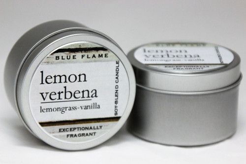 There are two silver, modern designed travel tins in the image. One tin is on it's side to show what the top of the label looks like on the lid: It says: lemon verbena underlined in the middle of the label, and is off set towards the left side in large text, lemongrass-vanilla are written below in a smaller font. The Blue Flame logo is at the top of the label. Soy-blend Candle is written on the right side in a vertical line. On the bottom of the label is written, Exceptionally Fragrant. The other tin is flat and shows that the tin is just silver without a wrap around label. The modern design uses pale hues and simplistic lines.